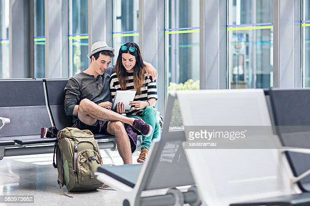 Young couple with digital tablet at airport