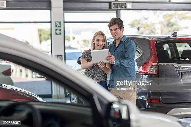 Young couple with digital tablet at car dealership