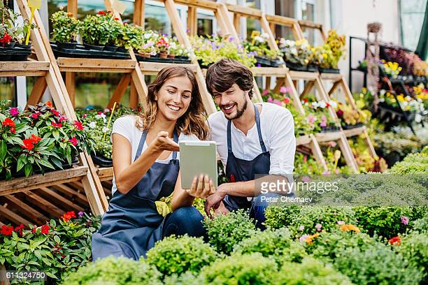 Young couple with digital tablet in garden center
