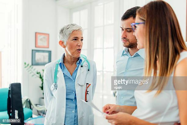 young couple with doctor in a consultation - human fertility stock pictures, royalty-free photos & images