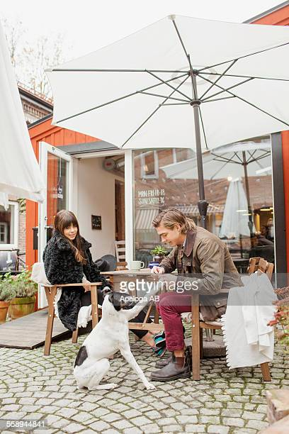 Young couple with dog at cafe backyard