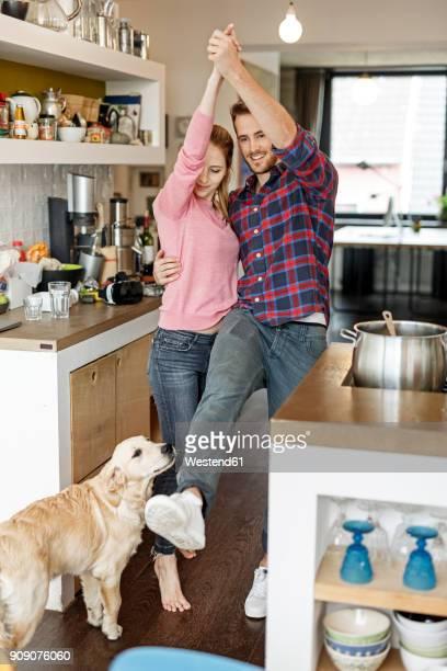 young couple with dog dancing in the kitchen - eén dier stockfoto's en -beelden