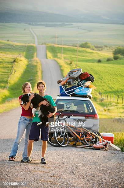 Young couple with dog in front of car loaded with vacation gear