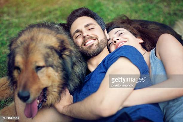 Young couple with dog is hugging on the grass