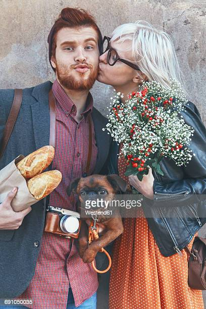 Young couple with dog kissing outdoors