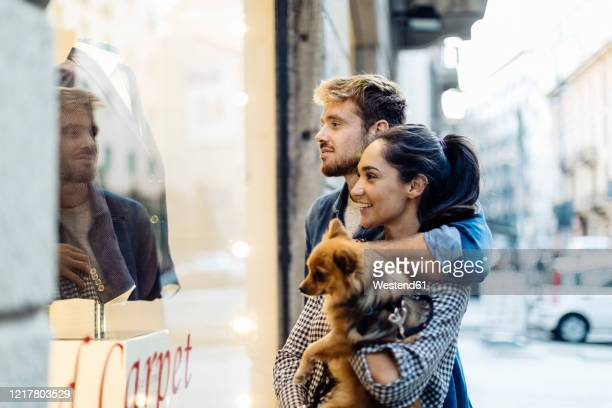 young couple with dog looking in shop window in the city - belgium stock pictures, royalty-free photos & images