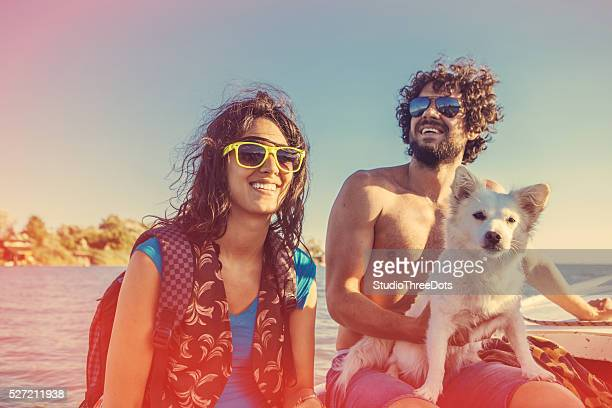 young couple with dog on boat