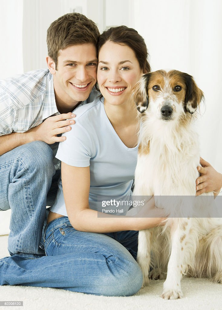 Young couple with dog, smiling : Stock Photo