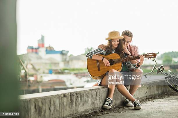 young couple with guitar - plucking an instrument stock pictures, royalty-free photos & images