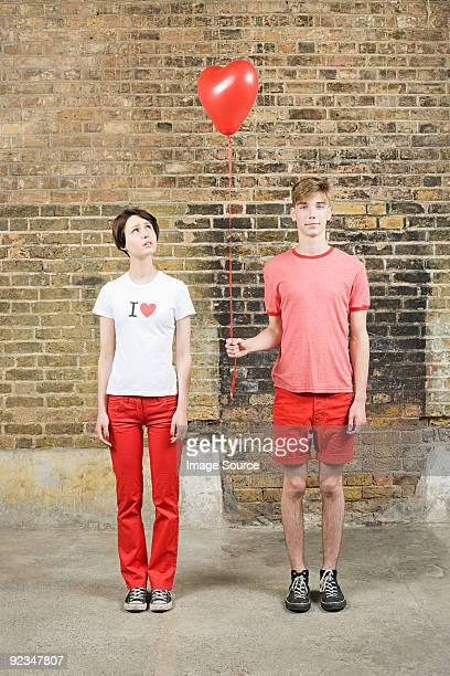 Junges Paar mit herzförmigen Ballons