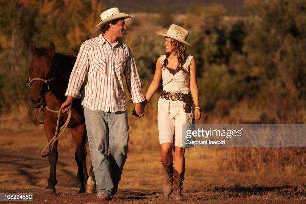 young couple with horse strolling - cowgirl hairstyles stock photos and pictures