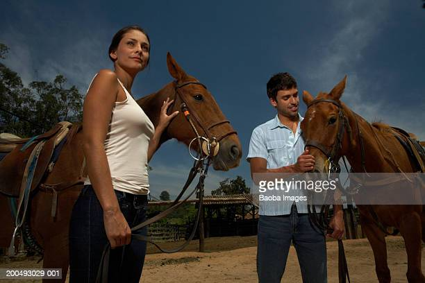 young couple with horses on ranch - rein stock pictures, royalty-free photos & images