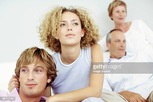 young couple with in-laws in the background - mother in law stock pictures, royalty-free photos & images