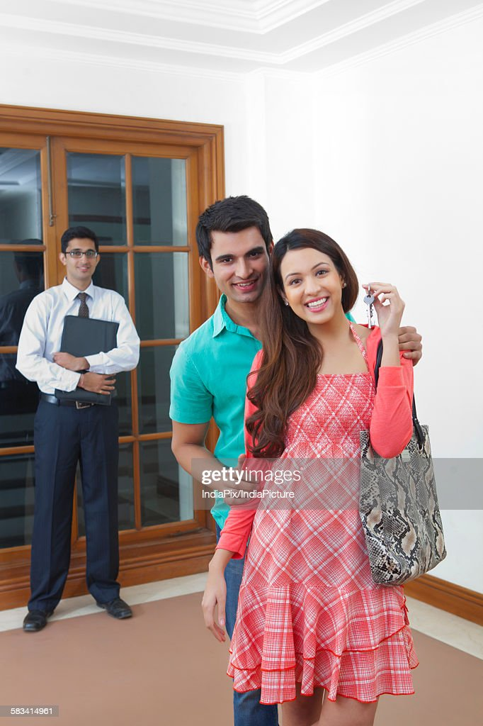 Young couple with keys of new house : Stock Photo