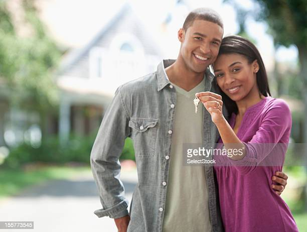 young couple with keys to new home - house key stock photos and pictures