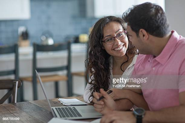 Young couple with laptop in kitchen