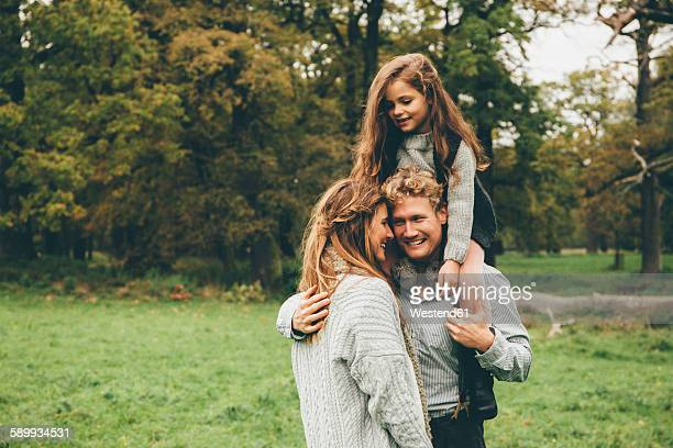 Young couple with little girl on her fathers shoulders at autumnal park