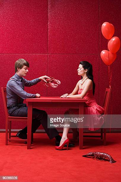 young couple with lobsters - red lobster restaurant stock pictures, royalty-free photos & images