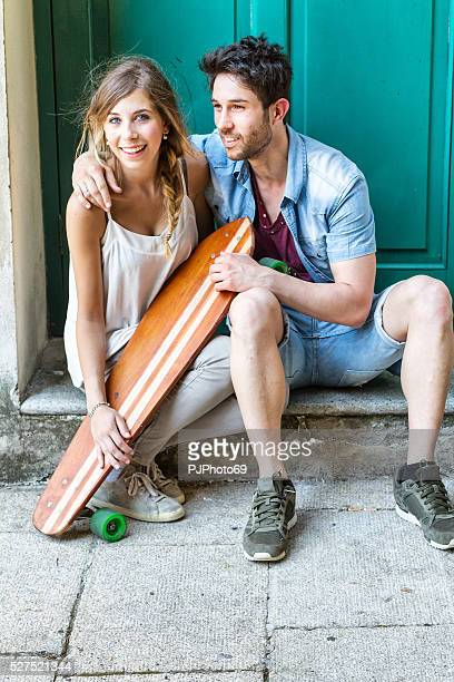 young couple with longboard - pjphoto69 stock pictures, royalty-free photos & images