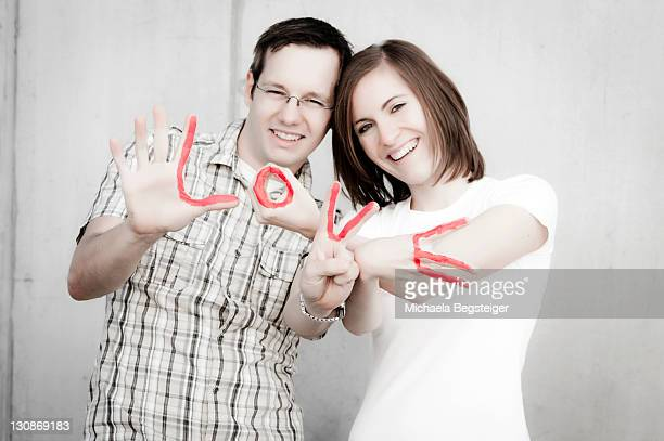 young couple with love lettering on their fingers - captions stock photos and pictures