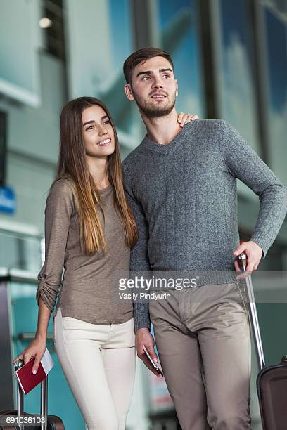Young couple with luggage and boarding passes at airport