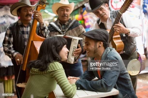 young couple with mariachi band - mariachi fotografías e imágenes de stock