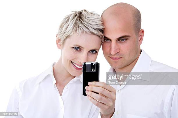 Young couple looking at mobile phone, close-up