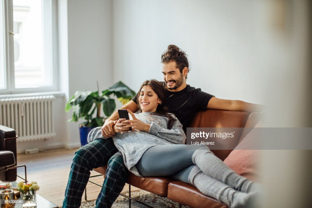 Young couple with mobile phone relaxing on sofa : Stock Photo