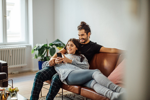 Young couple with mobile phone relaxing on sofa - gettyimageskorea