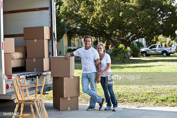 Young couple with moving van in driveway
