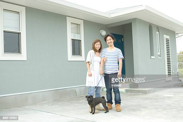 Young couple with pug smiling in front of house