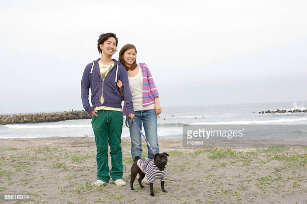 Young couple with pug standing on beach, smiling