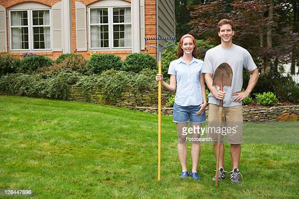 Young couple with rake and spade in garden