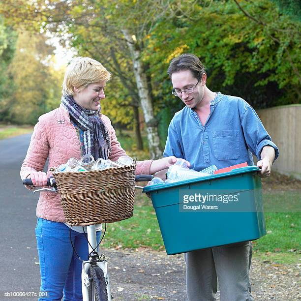 Young couple with recycling on roadside