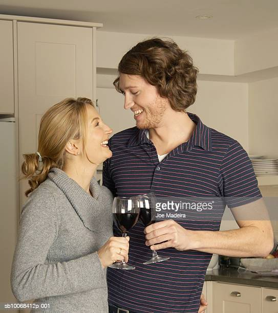 Young couple with red wine in kitchen