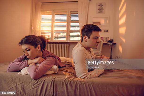 若いカップル問題に関係に横たわっているベッドを備えています。