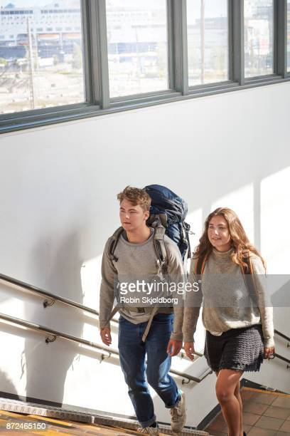 Young couple with rucksacks walking up stairs in trainstation