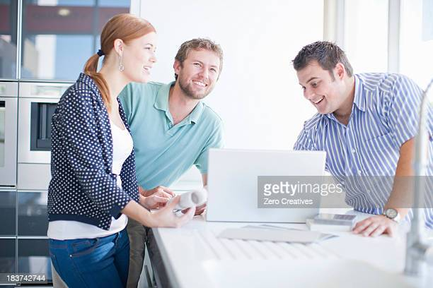 Young couple with salesman in kitchen showroom