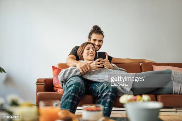 young couple with smart phone relaxing on sofa - saamhorigheid stockfoto's en -beelden