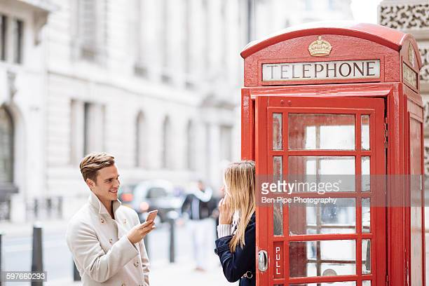 young couple with smartphone next to red phone box, london, england, uk - red telephone box stock pictures, royalty-free photos & images