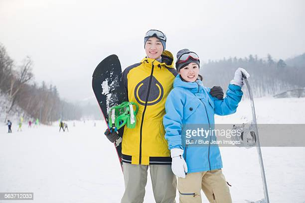young couple with snowboards on the snow - harbin winter stock pictures, royalty-free photos & images