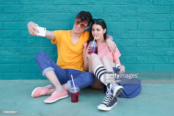 young couple with soft drinks taking selfie with smartphone in front of blue brick wall - vestido colorido - fotografias e filmes do acervo