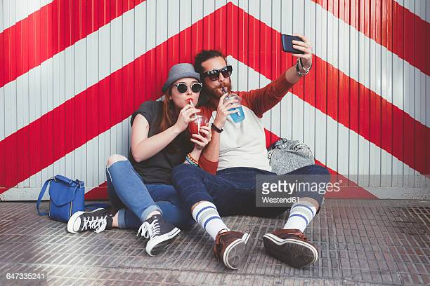 Young couple with soft drinks taking selfie with smartphone