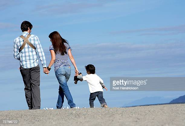 young couple with son (3-4 years) walking on beach, rear view - 25 29 years stock pictures, royalty-free photos & images