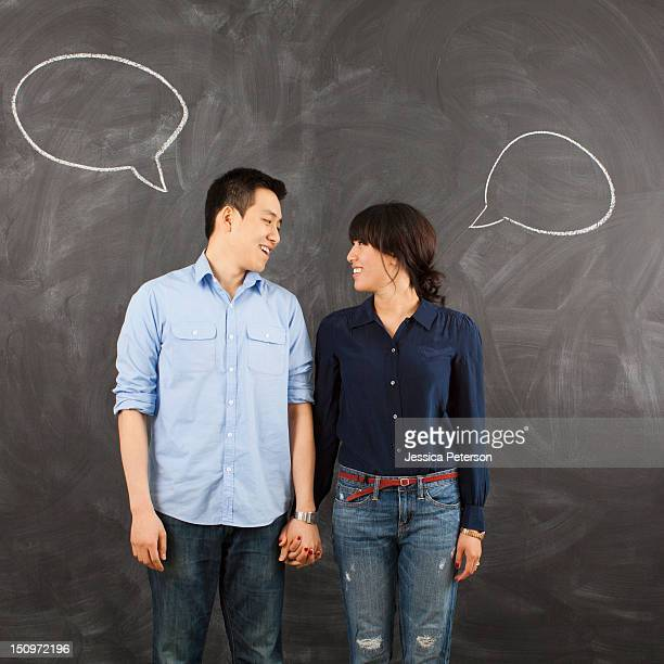 Young couple with speech bubbles on chalkboard, studio shot