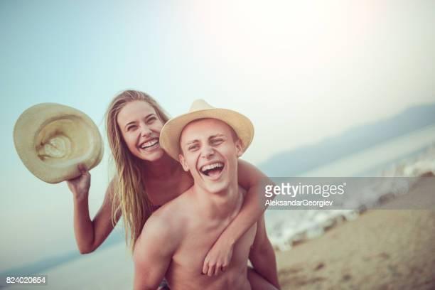Jeune Couple avec des chapeaux de paille ayant un Piggyback Ride sur la plage