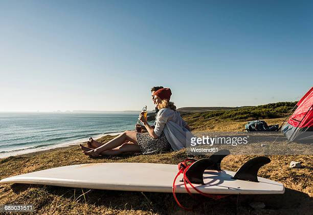 Young couple with surfboard camping at seaside