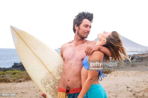 Young couple with surfboard on the beach
