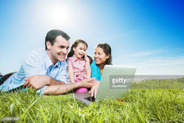 Young couple with their daughter using a digital tablet.