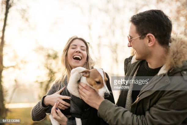 young couple with their jack russell puppy - people photos stock photos and pictures